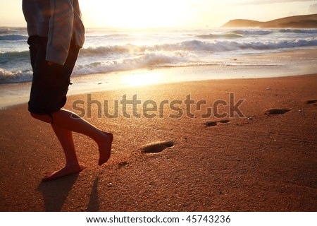 A girl walking on a beach in Cornwall