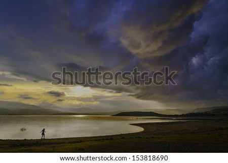 A girl walks along the shore of a lake as a large storm comes in. Sardinia Italy/stormy skies on a lake - stock photo
