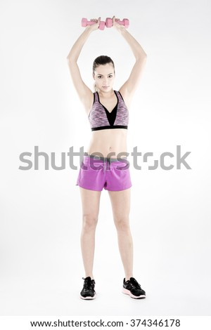 a girl warming up her shoulders with light weights, standing shoulders press - stock photo
