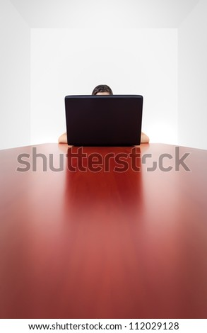 A girl (we can only guess so much) behind a laptop screen, sitting on the far end of a long, shiny table. The image conveys the isolation and anonymity from electronic devices and the Internet. - stock photo
