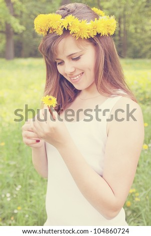 A girl wearing a crown holding a dandelion to a bee - stock photo