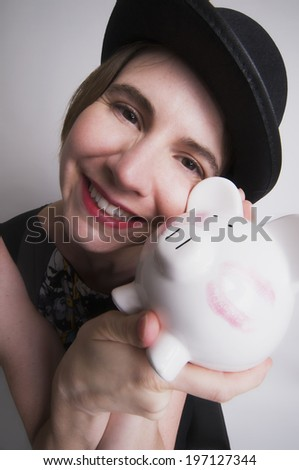 A girl wearing a hat and holding a piggy bank.