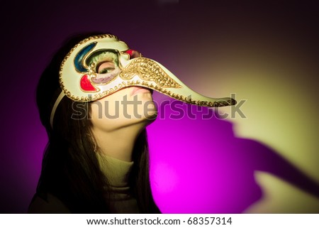 A girl wearing a venetian mask featuring a large nose, looking at camera. The shadow of her face (plus the mask's nose) is projected on the background. Illuminated using yellow and magenta spotlights. - stock photo