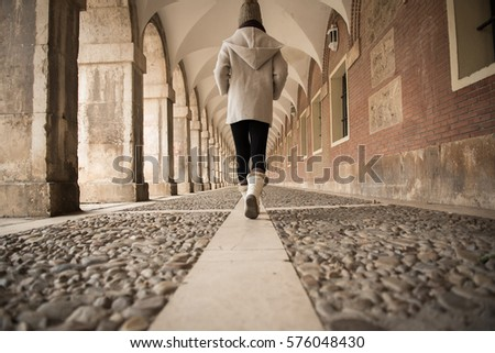 A girl wearing a woolly hat walks on a cobblestone floor under an archway in the Royal Palace Of Aranjuez, Madrid, Spain, with the cobblestone floor and tiles visible on the background