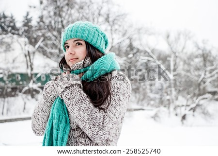 A Girl Wearing Warm Winter Clothes And Hat Blowing Snow In Winter Forest, horizontal - stock photo