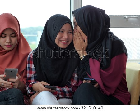 A girl whispering to a smiling friend while another is left out. - stock photo