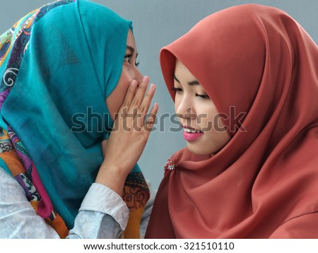 A girl whispering to her friend. - stock photo