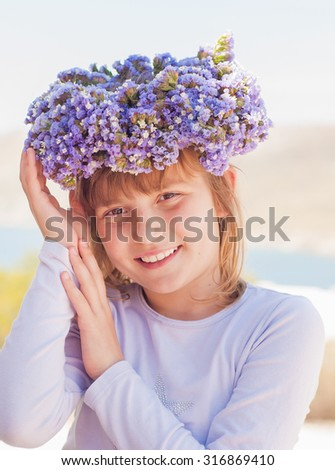 A girl with a beautiful wreath with lilac flowers - stock photo