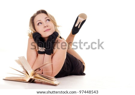 A girl with a book lying on a light background