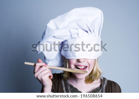 A girl with a chef's hat over her eyes holding a wooden spoon to her mouth. - stock photo