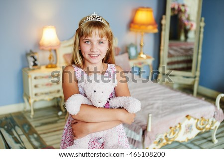 A girl with a crown on his head hugging a toy bear at home