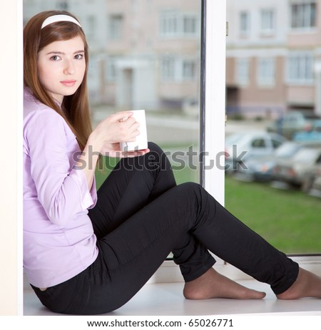 a girl with a cup is sitting on the window-sill - stock photo