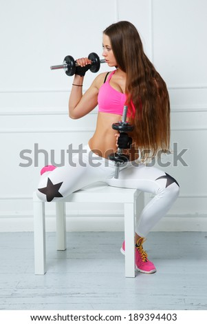 A girl with a dumbbell wearing a pink bra