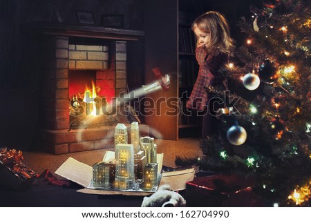 A girl with a gift by the fireplace on Christmas Eve