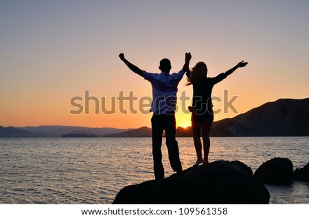 A girl with a guy raised his hands to the sky and watching the sunset at the beach - stock photo