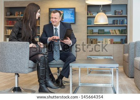 A girl with a man in a suit sitting on a chair and discuss business