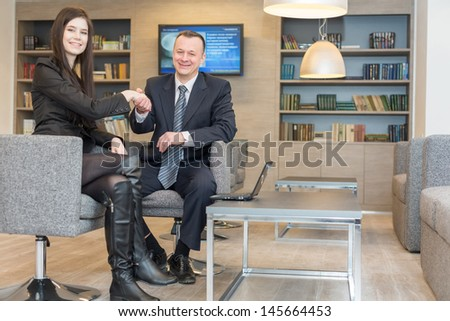 A girl with a man in business suits shaking hands