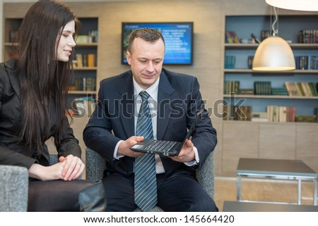 A girl with a man in business suits sitting on chairs with notebook, focus on a man.