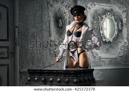 A girl with a perfect waist, in white lingerie and cap standing in a long coat with a whip