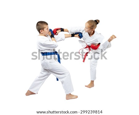 A girl with a red belt hits a boy with blue belt in the head - stock photo