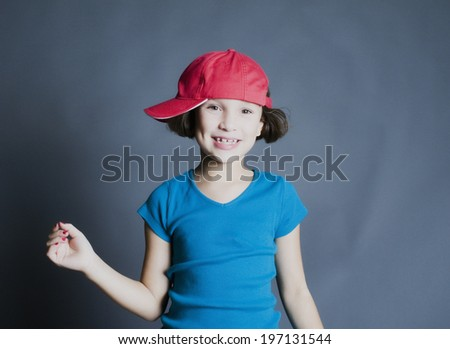 A girl with a red cap turned sideways smiles and waves.