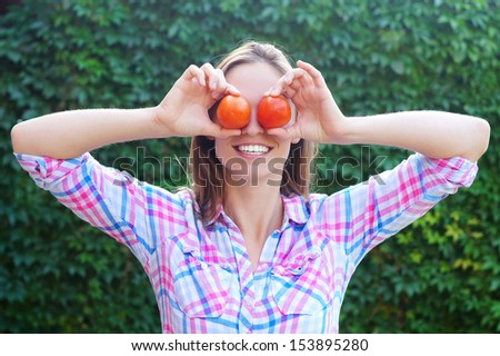 a girl with a ripe red tomato - stock photo