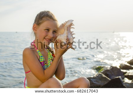 A girl with a seashell by the sea