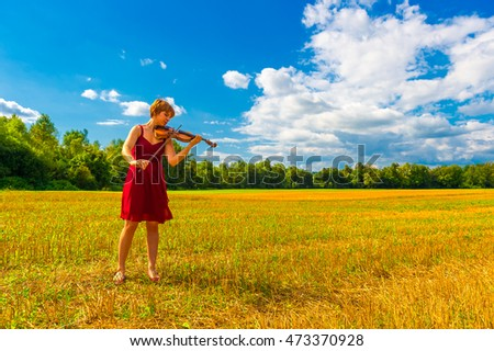 A girl with a violin on the field.