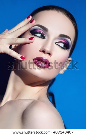 A girl with bright makeup. The fingers on her face. Blue background.