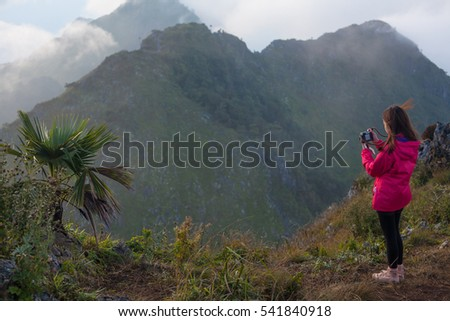 A girl with her camera shooting photograph at the highest peak of Chiang Dao mountain top, Thailand