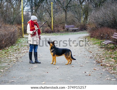 A Girl with her Dog Playing in the Park/ Selective Focus