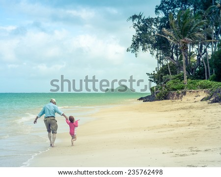 A Girl With Her Grandad On A Tropical Beach - stock photo