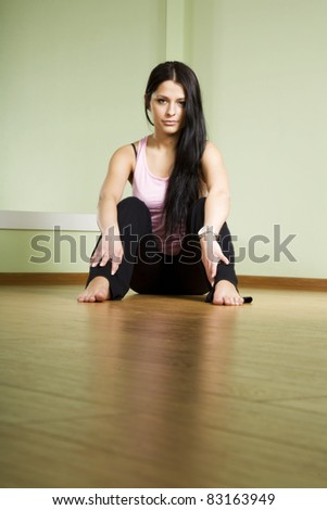 A girl with long black hair sitting on the floor and thinks