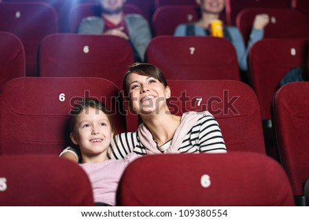 A girl with mother spending time together at the cinema - stock photo