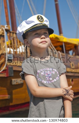 A girl with pigtails, wearing a cap, with a tattoo is about the ship and looks into the distance