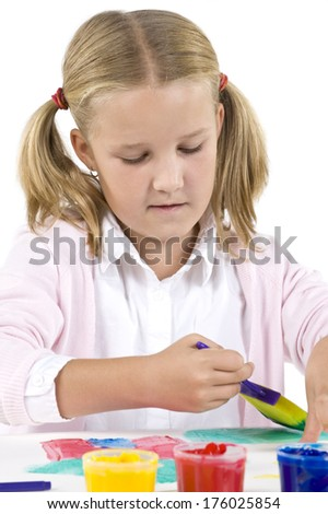 A girl with ponytails painting with colored paints.