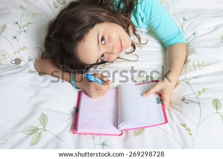 A Girl writing is diary in bed  - stock photo