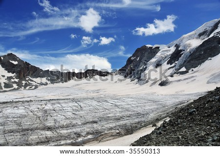 a glacier filling a large bowl in the mountains with mare's tails clouds above. Global warming is melting the glaciers and raising sea levels - stock photo