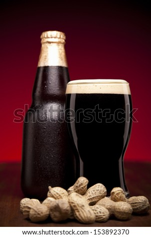 A glass, a bottle of beer and a hand full of peanuts. - stock photo