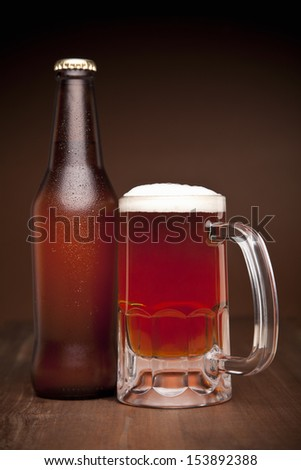 A glass and a bottle of beer on a wooden table. - stock photo