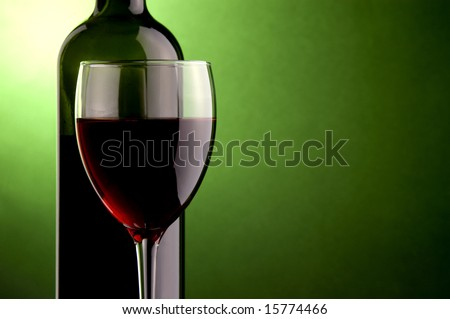 a glass and a bottle red wine