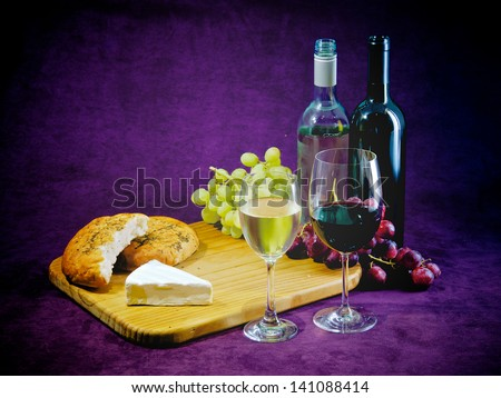 A glass and bottle of red and white wine, with bread grapes and cheese, plenty of room for text - stock photo