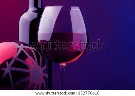 a glass and bottle of rose wine and christmas red ball decor - stock photo