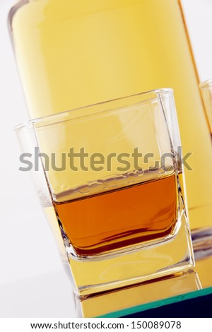 a glass and bottle of whiskey  on glass table against white background