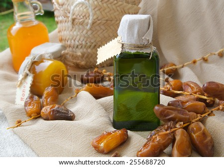 A glass bottle of dates seeds oil. Dates  in the background - stock photo
