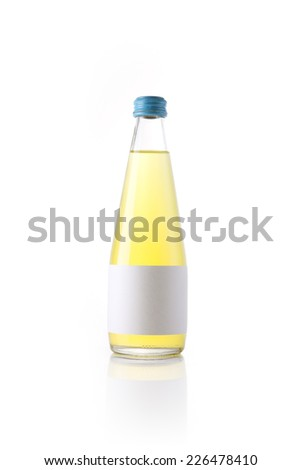 A glass bottle with yellow soft drink with blank label reflective bottom isolated white. - stock photo