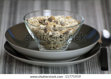 A glass bowl of oats and raisons with spoon against a Pattern linen background.