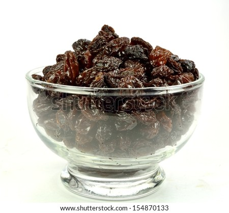 A glass bowl of raisins on a white background.