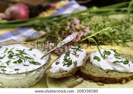 A glass bowl with fresh herb cheese and two slices of bread. In the background more herbs and flowers.   - stock photo
