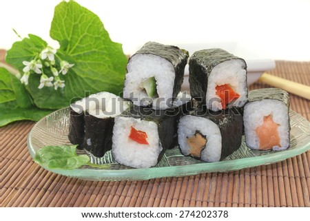 a glass bowl with sushi and wasabi leaves - stock photo